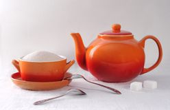 Orange teapot and sugar bowl on a white background stock image