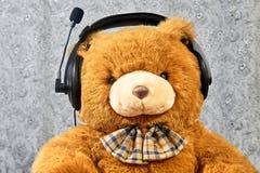 Orange teddy bear listening music in headphones Royalty Free Stock Photos