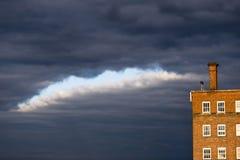 Orange tegelstenbyggnad med fönster på en mörk molnig himmel Royaltyfri Fotografi