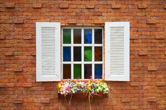Orange tegelstenvägg och wood fönster för vit med färgrika blommor Royaltyfria Foton