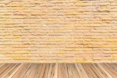 Orange tegelstenvägg som en utmärkt texturerad bakgrund på det wood golvet Arkivbild