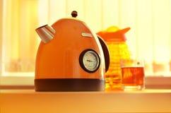 Orange tekanna på köksbordet royaltyfri bild