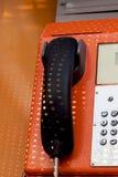 Orange telephone receiver with shawdow light. Royalty Free Stock Image