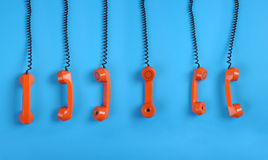 Orange telephones over blue background. Close-up large group of orange telephones over blue background Stock Image