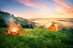 Orange tent and bonfire over the misty river. An orange tent and fire on hill above teak covered with a morning mist. Dramatic dawn sky. summer landscape. The royalty free stock photos