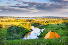Orange tent on the high bank of the river stock photography