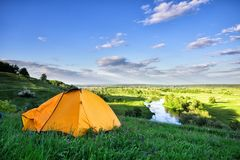 Orange tent on hill above the river Royalty Free Stock Photography