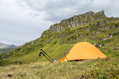 Orange tent in the mountains and trekking pole Stock Photo