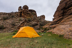 Orange tent near a huge rock. Stock Photos