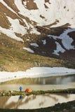 Orange tent near lake in mountains at sunset Royalty Free Stock Photo