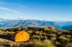 Orange tent in front of mounatin range on New Zealand` Roys Peak stock photos