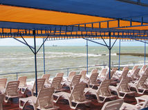 Orange tent. Plastic chairs under orange tent on the beach stock photos