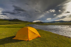 Orange tent on the river bank at sunset Stock Image