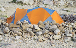 Orange tent on the rocks in the mountains. Orange and gray tent on the rocks, behind the stone wall in the mountains royalty free stock images