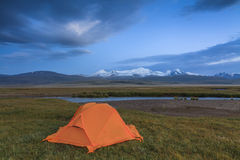 Orange tent on the shore of the lake Stock Photo