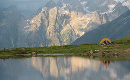 Orange tent and tourists near mountain lake Royalty Free Stock Images