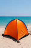 Orange tent on a white beach. An orange tent on a white beach with crystal clear water on the background Stock Images