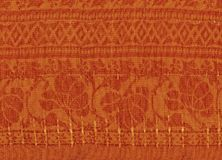 Orange textile background with golden patterns. royalty free stock photos