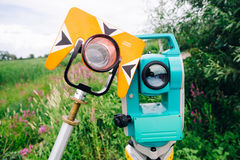 Orange theodolite prism and blue surveying equipment total station on  a background of lake Stock Image