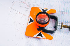 Orange theodolite prism lies on a background geodetic maps of the area Stock Photos