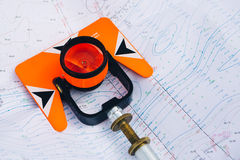 Orange theodolite prism lies on a background geodetic maps of the area Royalty Free Stock Image
