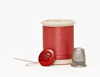 Orange thread, button, thimble, and needle Stock Photos