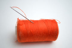 The orange thread with a needle. On a white background Stock Photos