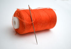 The orange thread with a needle. On a white background Royalty Free Stock Images