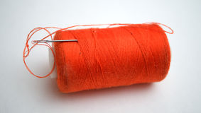 The orange thread with a needle. On a white background Royalty Free Stock Photography