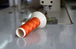 Orange thread in the thread roll put horizontal on the sewing machine. Royalty Free Stock Photos