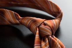 Orange tie knot. Elegant casual orange neck tie knot on black table Royalty Free Stock Photos