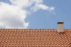 Orange tile roof with chimney over a blue sky Royalty Free Stock Images