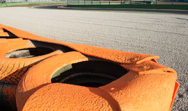 Orange tire barrier close up on motor sport circuit Stock Images