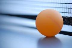 Orange Tischtenniskugel auf blauer Tabelle mit Netz Lizenzfreie Stockbilder