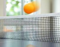 Orange Tischtenniskugel, die über Netz sich bewegt Stockbilder
