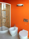 Orange toilet with shower. Orange shower and toilet with bidet and mosaic tiles Stock Photos