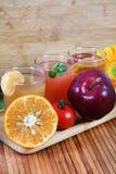 Orange tomato and apple juice Stock Photos