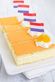 Orange tompouce, traditional Dutch pastry, on a rustic table Royalty Free Stock Images