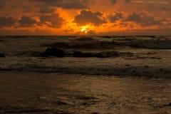 Orange toner av solnedgången reflekterade i vågorna royaltyfri fotografi