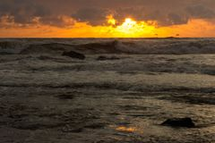 Orange toner av solnedgången reflekterade i vågorna fotografering för bildbyråer