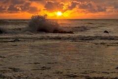 Orange toner av solnedgången reflekterade i vågorna royaltyfri bild