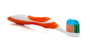Orange toothbrush and toothpaste on white Stock Photo
