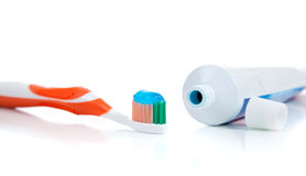 Orange toothbrush with toothpaste on white Royalty Free Stock Photography