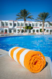 Orange towel on a sun lounger on the background of the pool Royalty Free Stock Photography