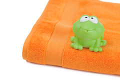 Orange towel and toy frog Stock Photography