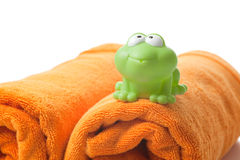 Orange towels and toy frog Stock Photography
