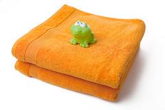 Orange towels and toy frog Royalty Free Stock Images