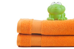 Orange towels and toy frog Stock Image