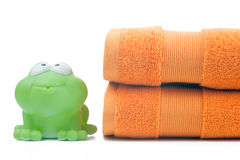 Orange towels and toy frog Royalty Free Stock Photos