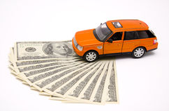 Orange toy car and USA dollars Royalty Free Stock Photos